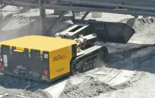 A mini dozer 48 under a bridge transporting dust